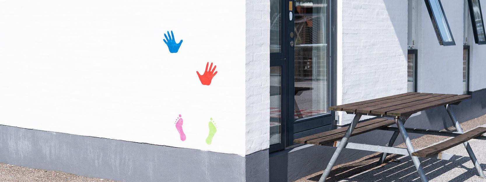 Farvede hænder og fødder malet på mur