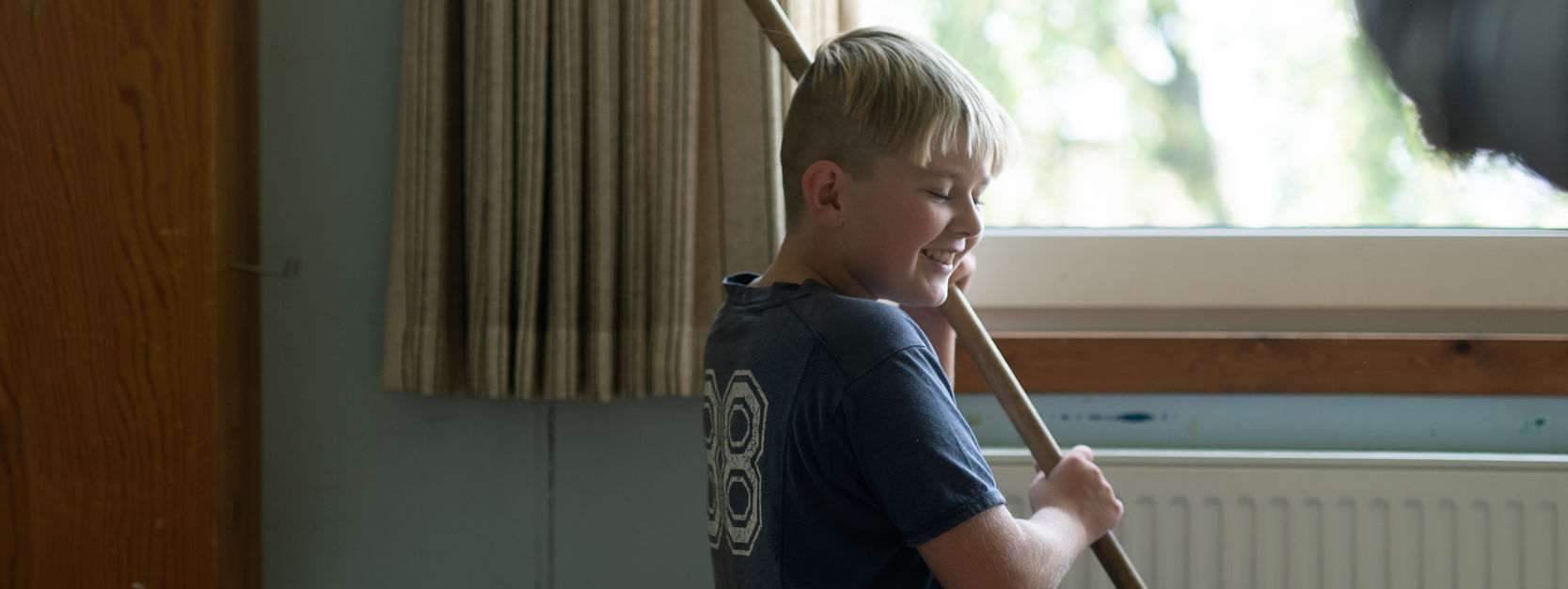 Glad dreng fejer gulvet